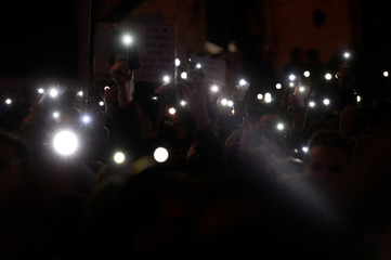 """Demonstrators hold lights during a protest called """"Let's stand for decency in Slovakia"""" in Bratislava"""