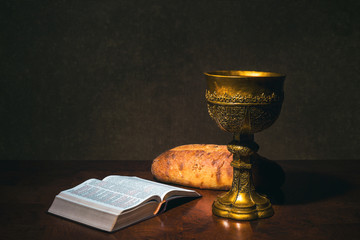 Goblet with wine bread and Holy Bible on a table