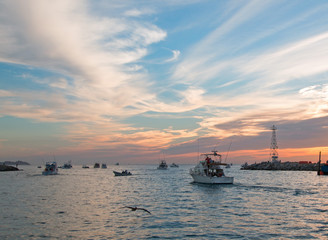 Fishermans sunrise view of fishing boat going out for the day past Lands End in Cabo San Lucas in Baja Mexico