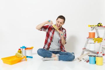 Fun woman in casual clothes sitting on floor with brush, instruments for renovation apartment room isolated on white background. Wallpaper, accessories for gluing, painting tools. Repair home concept.
