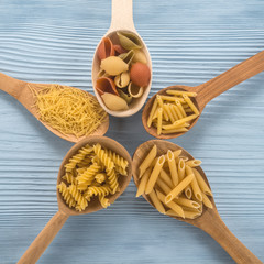 Samples of dry pasta in a wooden spoons