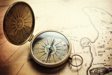 Wall Mural - Old vintage retro compass on ancient map background. Travel geography navigation concept background.