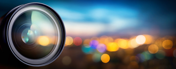 Camera lens with lense reflections on blur night city. Media and technology concept background.