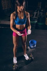 Fit woman standing with chalk powder in her hands