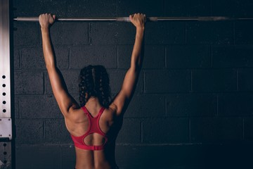 Fit woman exercising on a bar in the gym