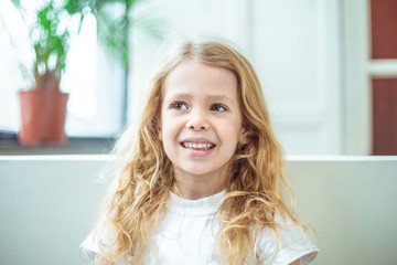 Portrait of a beautiful smiling little blond girl. A child sitting on the couch at home.