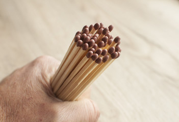 A bunch of wooden matchsticks held in human wrist closeup on wooden background