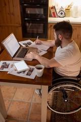Disabled man noting while using laptop