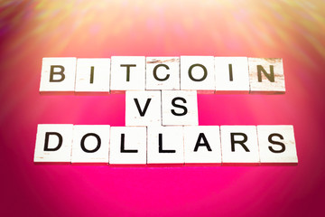 Wooden blocks on a red background spelling words Bitcoin vs dollars