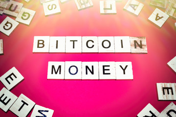 Wooden blocks on a red background spelling words Bitcoin money