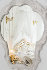 White berdroom reflection in clasiic mirror