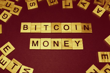 Wooden blocks on a brown background spelling words Bitcoin Money
