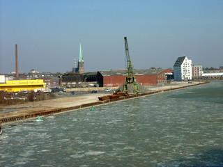 Alter grüner Hafenkran im Winter am Dortmund-Ems-Kanal mit Eisschollen in Münster in Westfalen im Münsterland