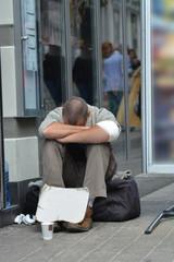 man sitting asking for money