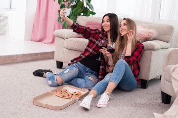 Let the good times roll! Cheerful young ladies making selfies while drinking wine and enjoying their leisure time at home.