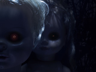 Two creepy faces of scary plastic dolls with fiery eyes, closeup.