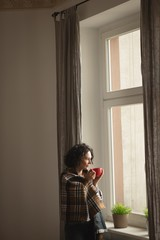 Woman having coffee in living room at home