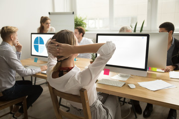 Rear view at businesswoman holding hands behind head resting after finishing work on computer in multiracial office, company manager employee relaxing or thinking taking short break at workplace