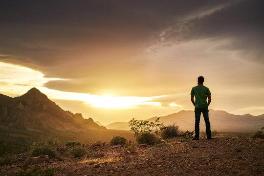 man watching golden sunset over mountains in nevada desert