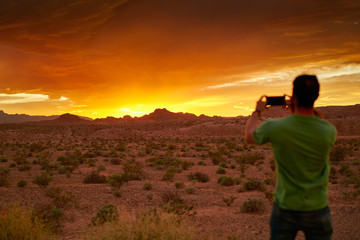 man taking photo with smartphone of very colorful sunset in nevada desert