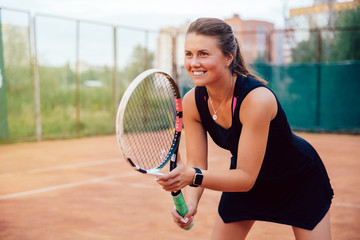 Tennis player. Attractive young woman standing with racket in ready stance to receive ball, while playing tennis. Dressed in black sportswear.
