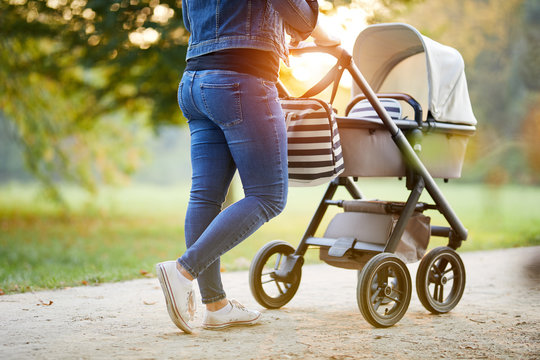 Woman with baby stroller walks in the park at sunset