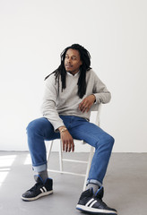 Portrait of black man sitting on a chair.