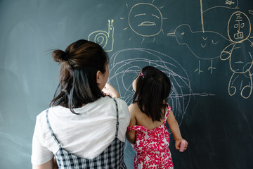 Toddler girl with her mother drawing on blackboard wall