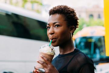 Stunning black woman drinking a beverage