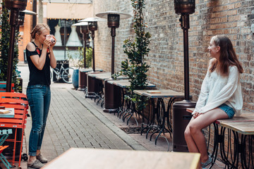 Two girls taking photos in an alley