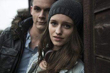Close-up portrait of teenage girl and young man outdoors, looking at camera, Germany
