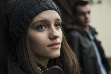 Close-up portrait of teenage girl outdoors, wearing hat and headphones around neck, with young man in background, Germany