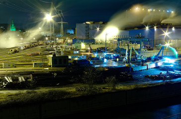 Steel hut in Völklingen in the Saarland in Germany at night in the foreground the Autonahn a620 and the river Saar, the photo shows the production of steel from scrap loaded in railway wagons