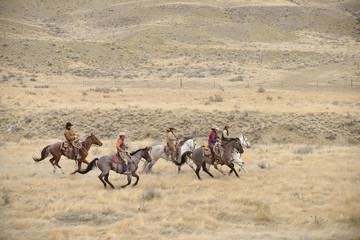 Cowboys and Cowgirls riding horse in wilderness, Rocky Mountains, Wyoming, USA