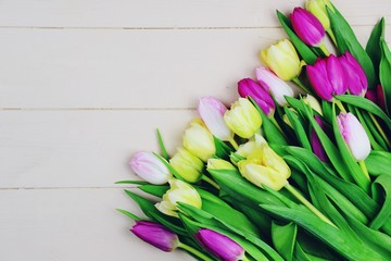Tulips on the light wooden background. Top view flowers