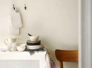Stack of Rustic Country Dishes with Cutting Boards Hanging on Wall in Kitchen