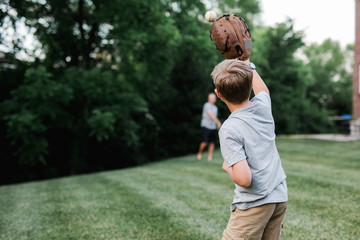 Father and son playing baseball in the backyard