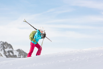 Woman walking uphill ski slope carrying her skis and poles