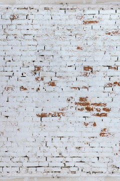 Brick wall whitewashed by lime, dirty and rubbed, traces of brush