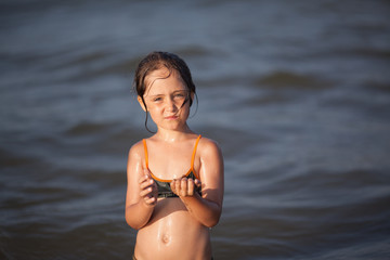 Little girl in bikini plays in the sea