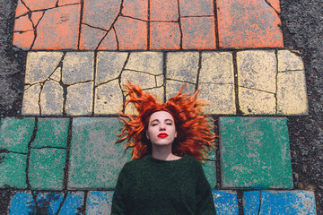Red haired woman lying on a colorful tile path