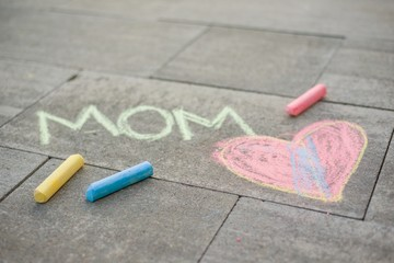 Happy Mother's Day. Child draws for her mother a picture surprise of crayons on the asphalt. LOVE MOM