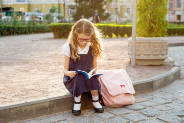 Young schoolgirl reading a book. Urban style background