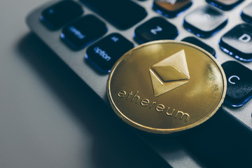 Ethereum gold coin on computer keyboard backlit