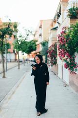 Muslim teenager using phone at street