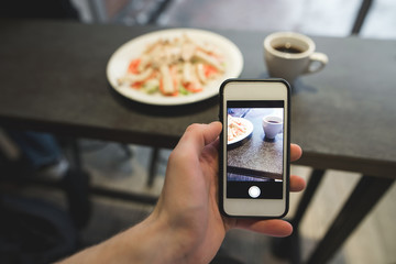 The hand with the phone makes a photo of the food in the restaurant. A salad and coffee photo on a smartphone