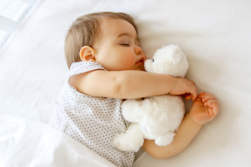 Cute little baby sleeping hugging his white teddy bear