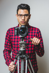 Young Photographer with a Digital Reflex Camera on a Tripod