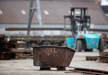 "A garbage bin with the words ""STEEL MY JOB!"" painted on it sits in a storage yard where structural steel is loaded onto a truck in the portlands of Hamilton"