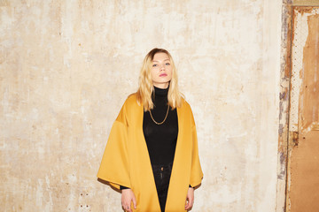 Sensual blonde girl in yellow coat over shabby wall.